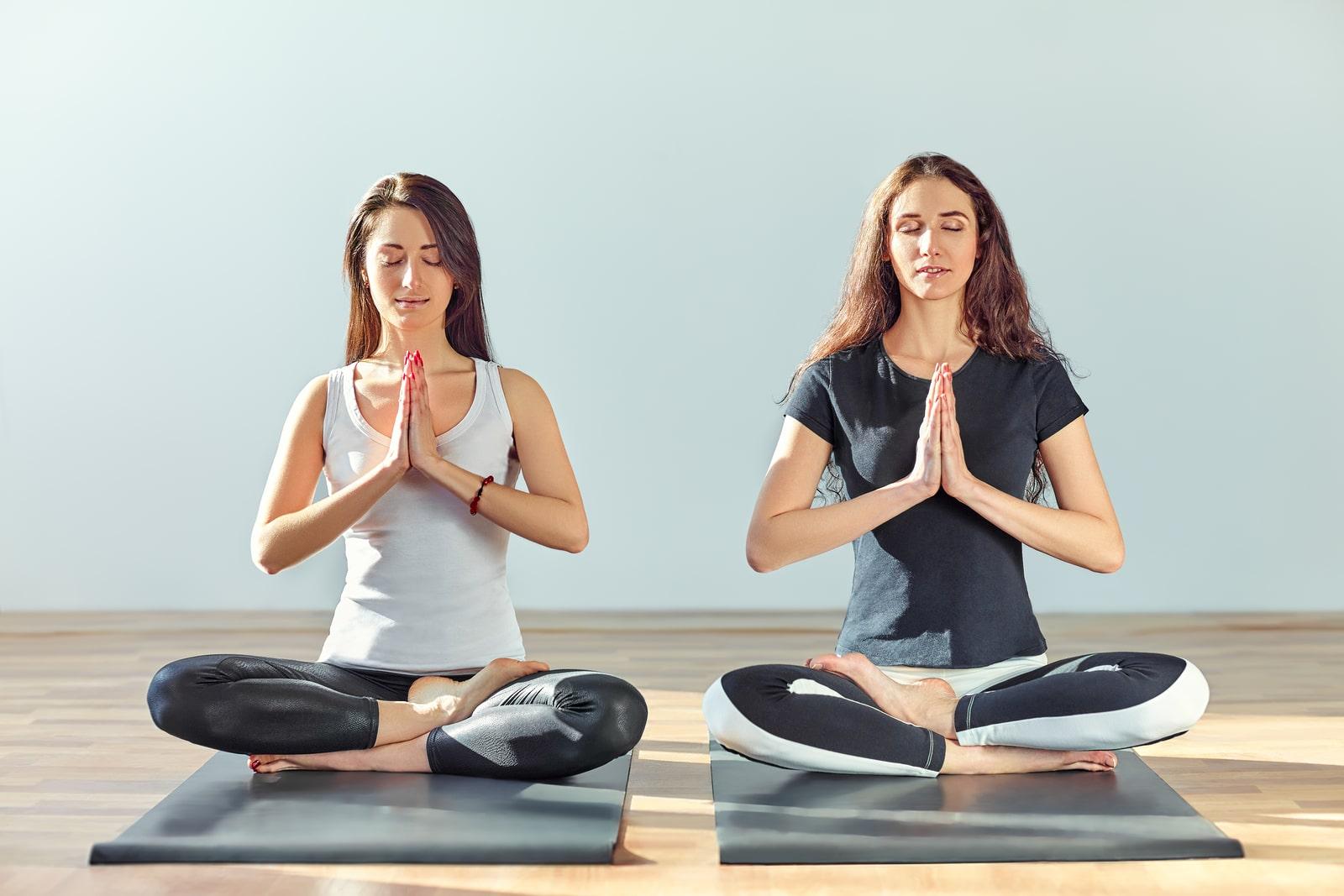 Duas mulheres jovens em posição de meditação e com as mãos em forma de namastê.