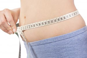 Girl in panties measuring her body with tape measure detail isolaled on white. Belly detail. Weight loss and diet.