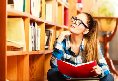 Education school concept. Clever female student hair ponytail girl blue glasses sitting on floor in college library with stack books. Indoor