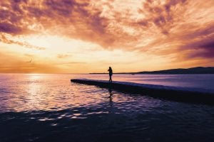 Woman walking on pier near the sea at sunset tranquil scene. Beautiful seascape