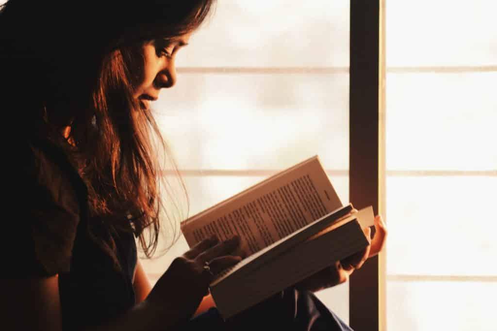 Mulher vista de perfil lendo um livro ao lado de uma janela.