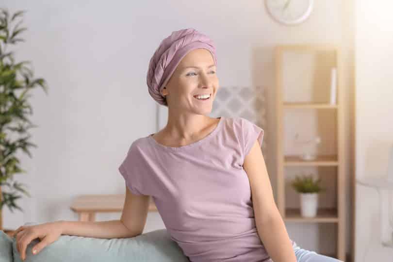 Mulher com lenço na cabeça sorri.