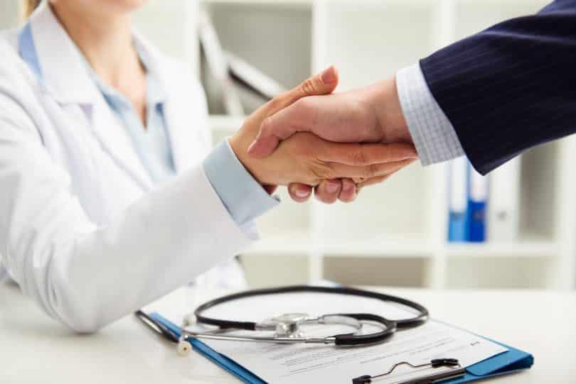 Médica e paciente de mãos dadas