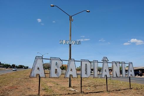 Placa indicando a cidade de Abadiânia, no meio de uma estrada, em Goiás.