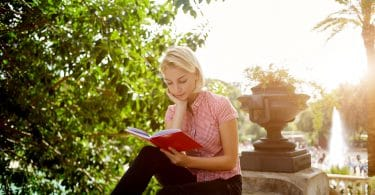 Young beautiful woman is reading book while sitting in the park in sunny spring day during her recreation time female student is learning in the fresh air before start lectures in university