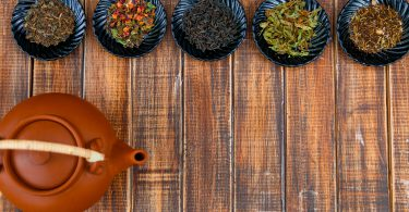 Different kinds of tea on plates near brown teapot on wooden background. Assortment of dry tea. Tea concept. Tea leaves. Frame. Copy space. Top view.