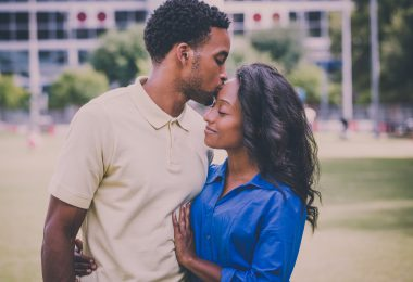 Closeup portrait of a young couple guy holding woman and kissing her forehead. Retro aged vintage look ** Note: Shallow depth of field
