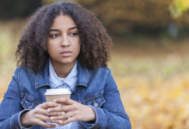 Beautiful mixed race African American girl teenager female young woman outside in autumn or fall looking sad depressed or thoughtful drinking coffee