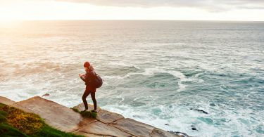 View from above of a woman reading text massage on cell telephone while standing against ocean background with copy space