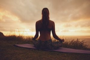 Silhouette rear view of young woman doing yoga meditation outdoors. Fitness female model sitting on exercise mat in lotus yoga pose during sunset.