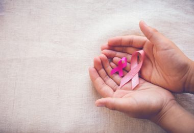 Hands holding Pink Ribbons toning background Breast cancer awareness and Abdominal cancer awareness