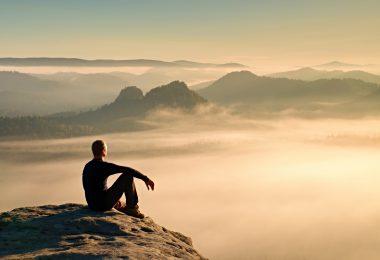 Hiker in black on the rocky peak. Wonderful daybreak in mountains heavy mist in deep valley. Man sit on the rock.