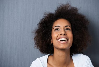 Laughing African American woman with an afro hairstyle and good sense of humour smiling as she tilts her head back to look into the air