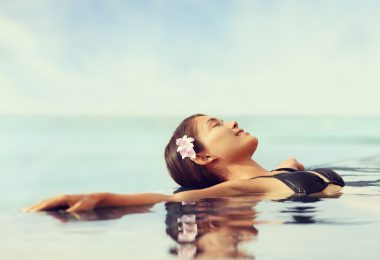 Luxury resort woman relaxing in infinity swim pool. Asian young adult lying down in swimming pool of beach resort for summer holidays or travel vacations.