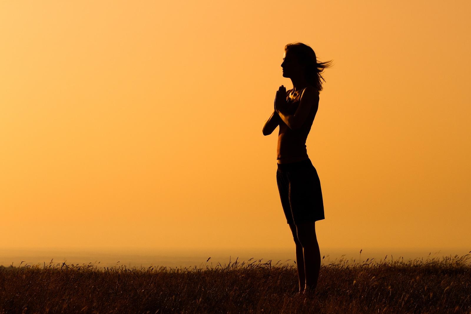 Mulher em pé em um campo. Ela está com as mãos juntas em forma de oração.
