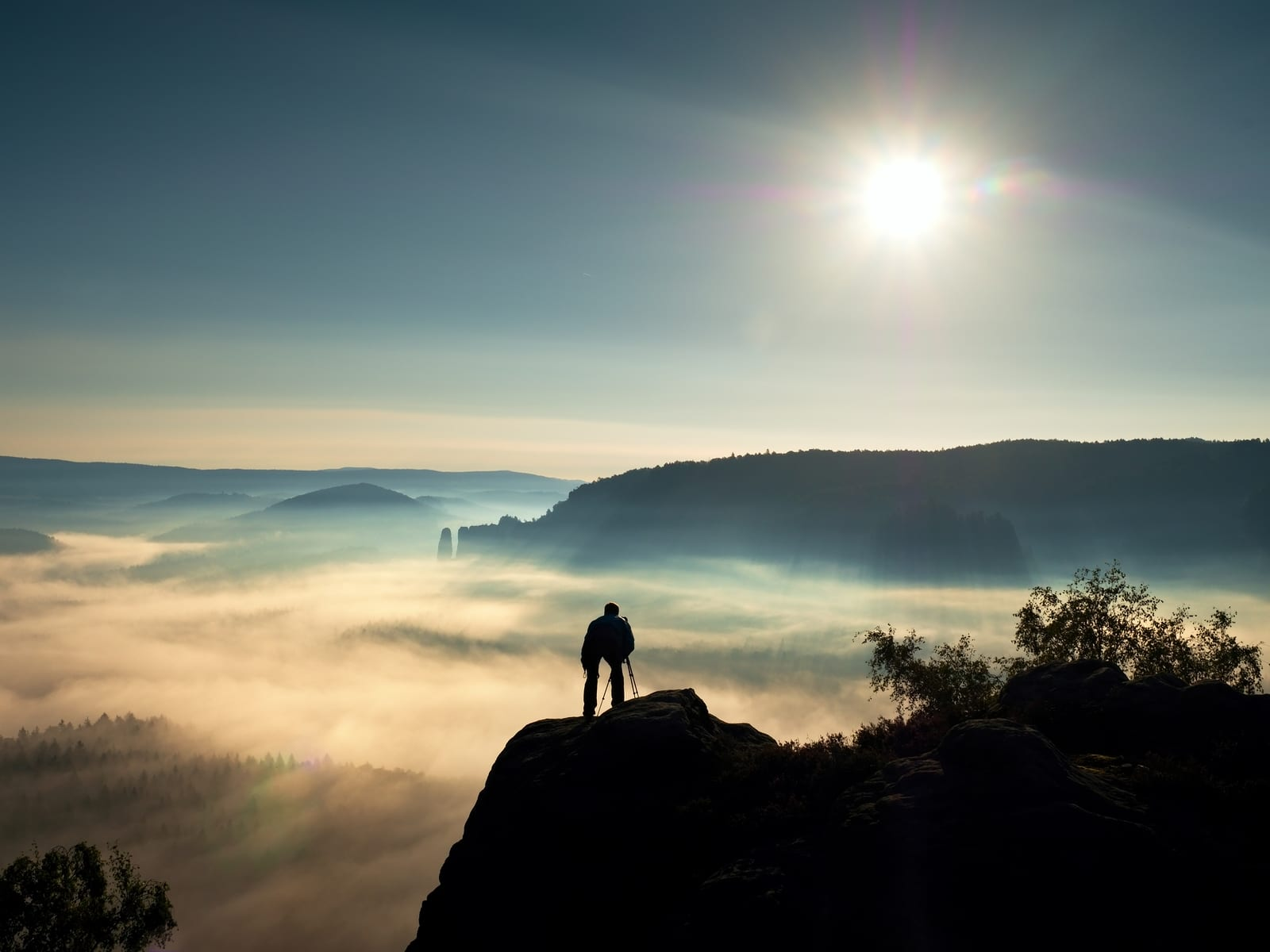 Nature photographer with tripod and camera on cliff and thinking. Dreamy fogy landscape orange misty sunrise in a beautiful mountains. Vivid and strong vignetting effect.