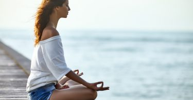 Woman meditating in Lotus Pose on pier with the sea view. Padmasana. Relax concept
