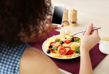 Woman eating delicious pasta in restaurant