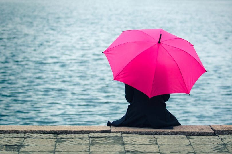 Woman sitting lonely with pink umbrella. Concept of taking a break, solitude and thinking with good copyspace on water. ** Note: Visible grain at 100%, best at smaller sizes
