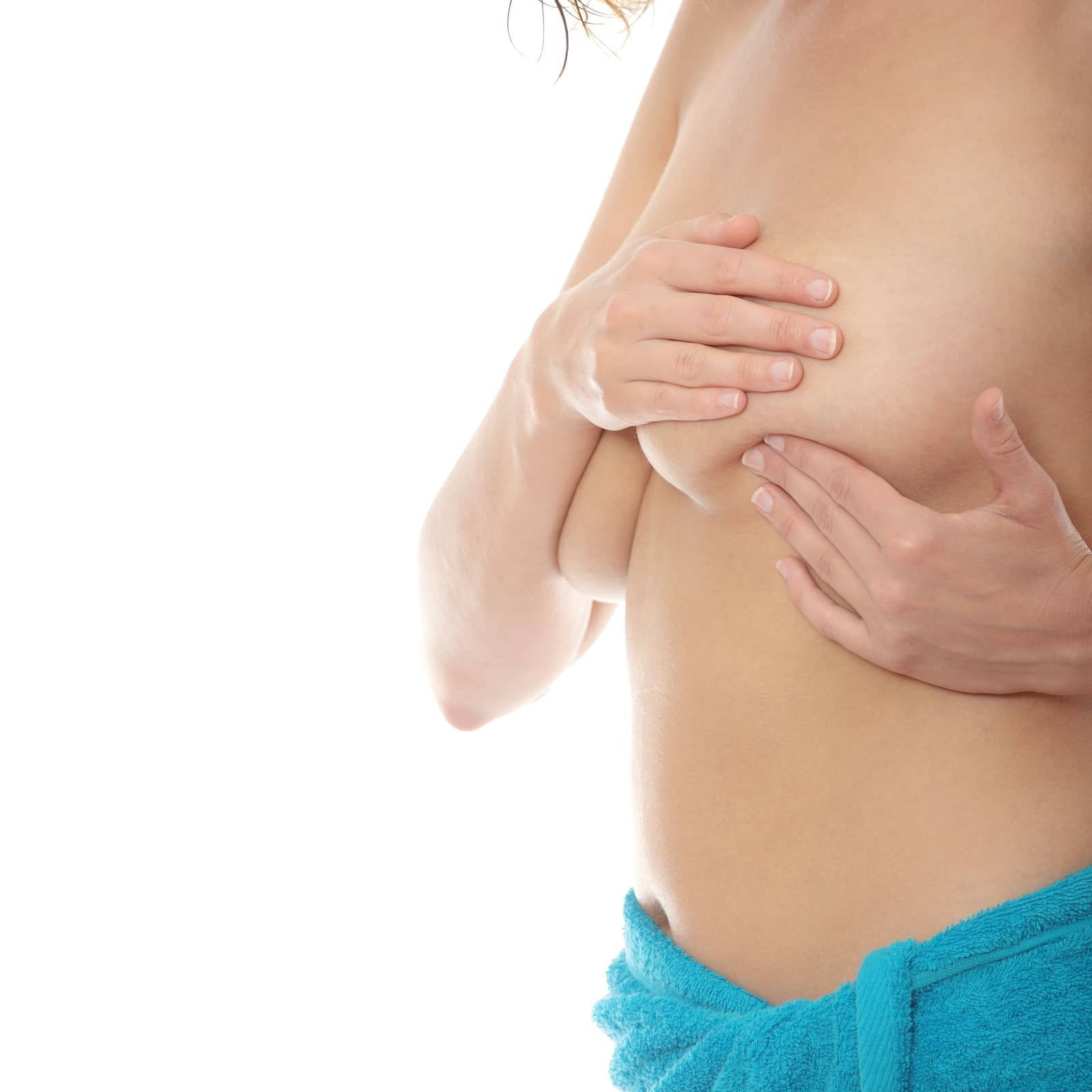 Young Caucasian adult woman examining her breast for lumps or signs of breast cancer