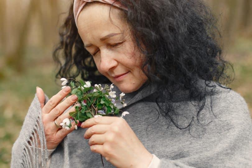 Mulher segurando flor de olhos fechados e sentindo seu aroma
