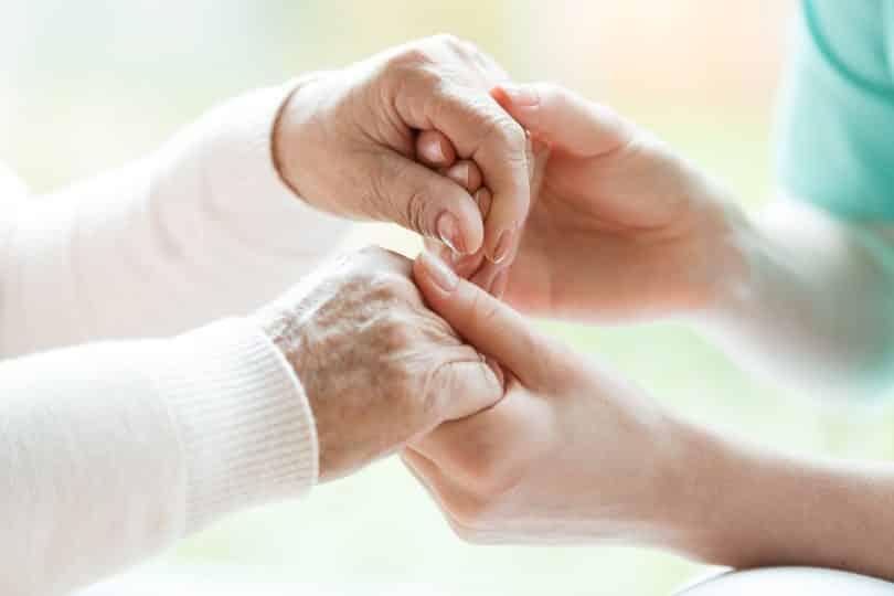 Mulher segurando mãos de senhora