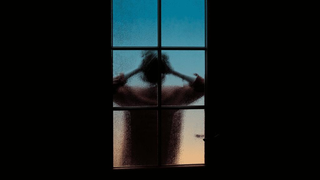 Silhueta de pessoa tentando enxergar algo por uma janela