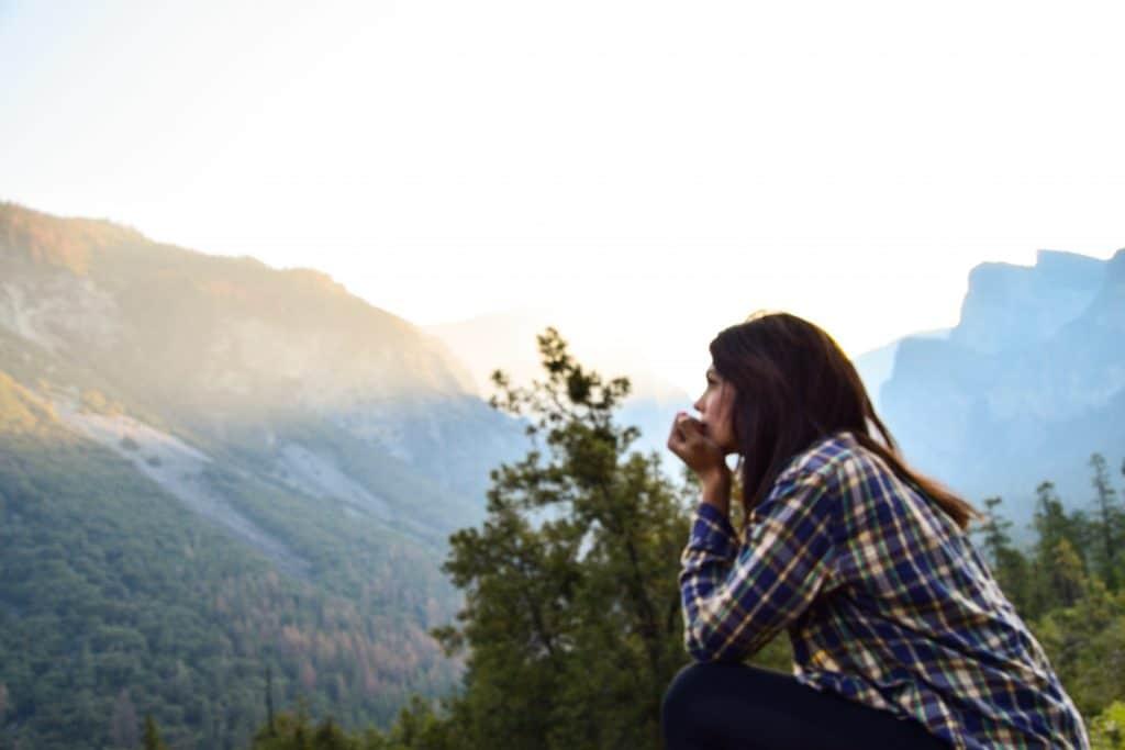 Mulher sentada em uma montanha pensativa
