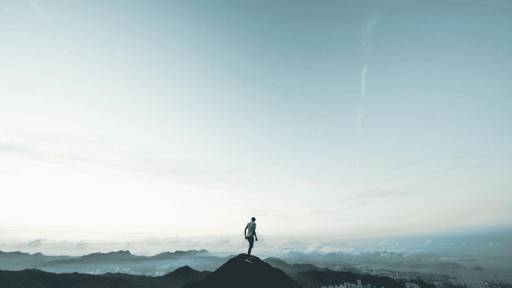 Homem sobre o topo de uma montanha observando o horizonte azul