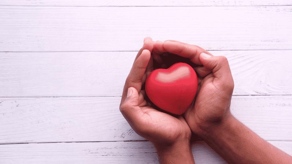 Pessoa segurando um coração na palma das mãos