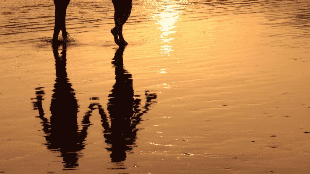 Silhueta de casal caminhando de mãos dadas na praia