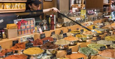 New York, USA - June 19, 2016: Female salesperson uses a long spoon to transfer spices in a spice shop in Grand Central Market in New York City