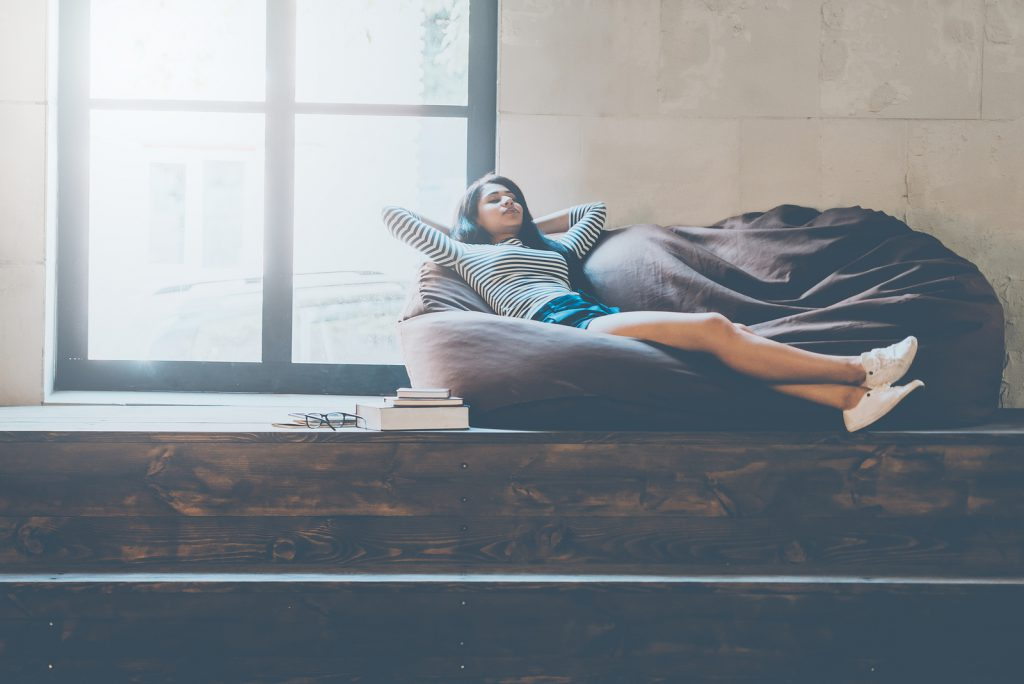 Time to relax. Beautiful young mixed race woman holding hands behind head and keeping eyes closed while lying on the comfortable couch and near the large window
