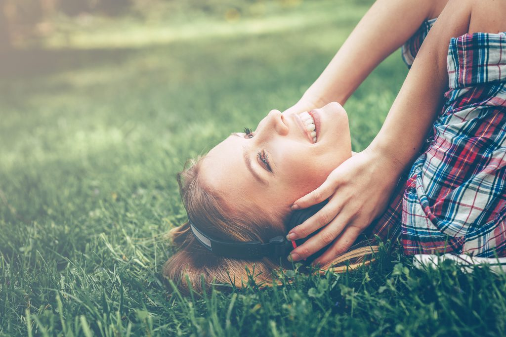 Enjoying her favorite music. Side view of beautiful young woman in headphones listening to the music and smiling while lying on the green grass