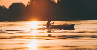 Meeting the best sunset. Side view of man kayaking on river with sunset in the background