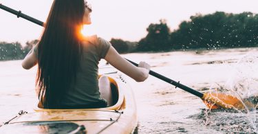 Enjoying perfect sunset on river. Rear view of beautiful young woman kayaking on river and with sunset in the background