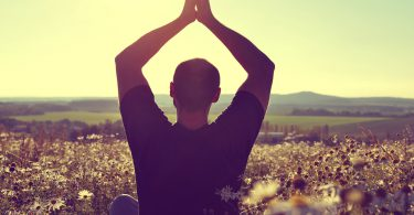 Silhouette of man practicing yoga on meadow at sunset.