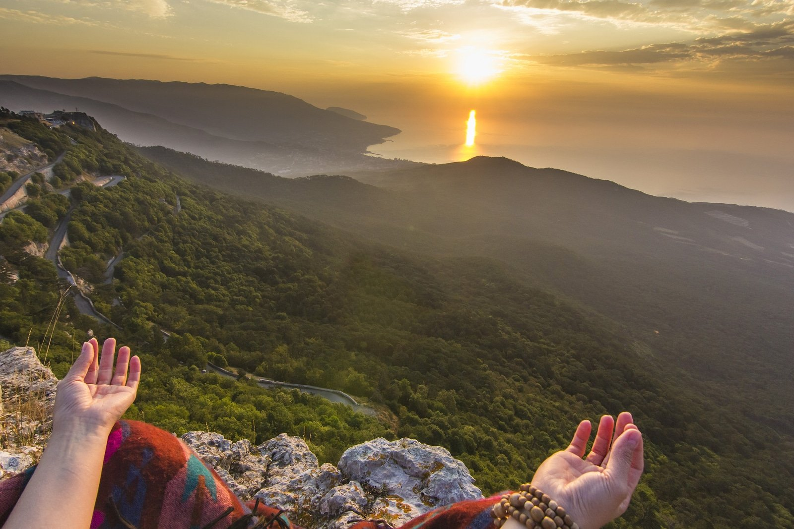 view from eyes of sitting girl in yellow sunrise in mountains above Black sea in Crimea