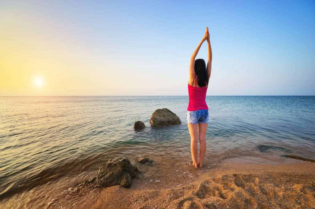 Slender woman girl on seashore deals morning gymnastics. Fitness on the beach. Fitness and gymnastic composition