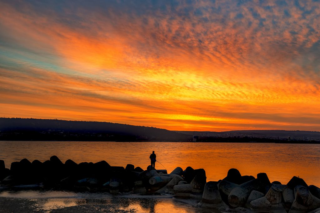Fishing and fisherman at amazing sea sunset