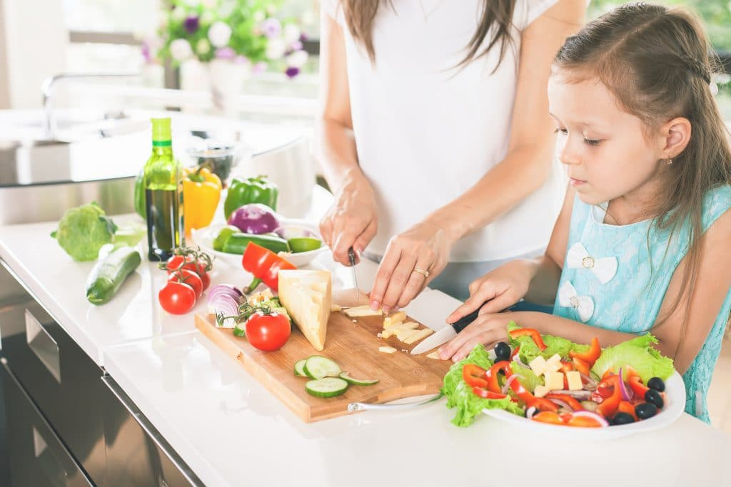 Cute little girl cooking with her mother. Healthy food, cooking healthy salad with vegetables ingredients. Mom and daughter cooking together. Recipe food for baby or child