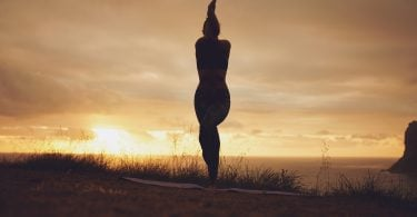 Silhouette of a woman practicing yoga Garudasana Eagle pose. Fitness female standing on mat doing yoga with her arms and legs crossed.