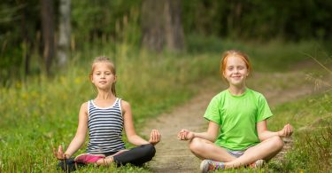 Two little cute yoga girls sitting in Lotus position outdoors.
