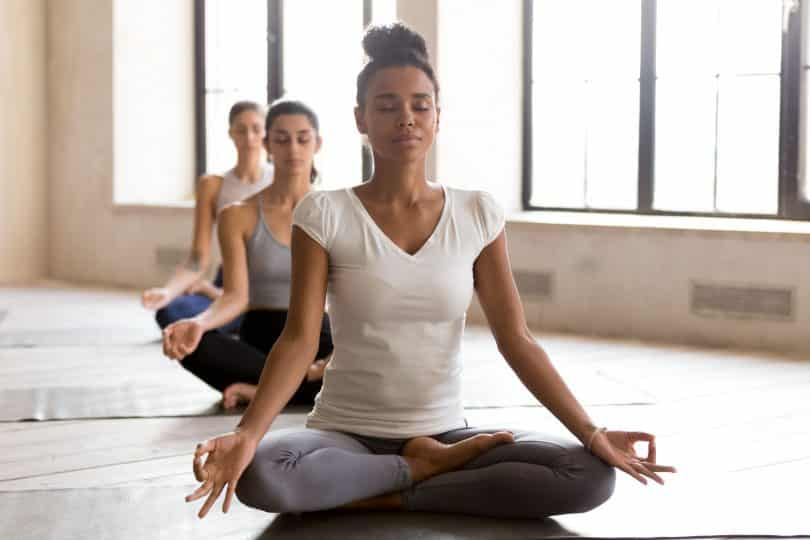 Mulher sentada em posição de lótus em aula de meditação.
