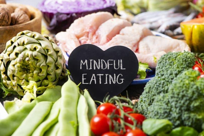 """Bancada com carnes e legumes e uma plaquinha preta escrito """"mindful eating""""."""