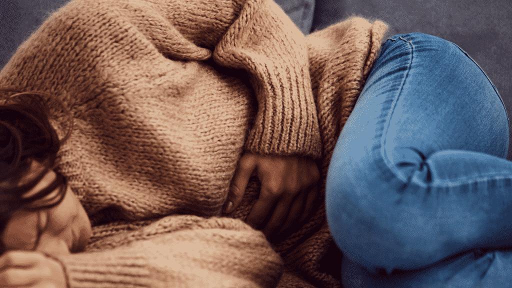 Mulher deitada no sofá com dor no estômago
