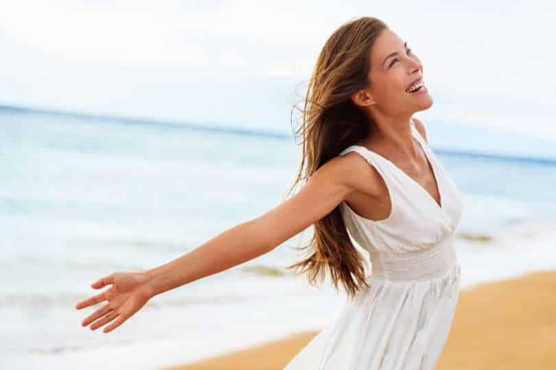 Mulher de vestido na praia, sorrindo com os braços abertos.