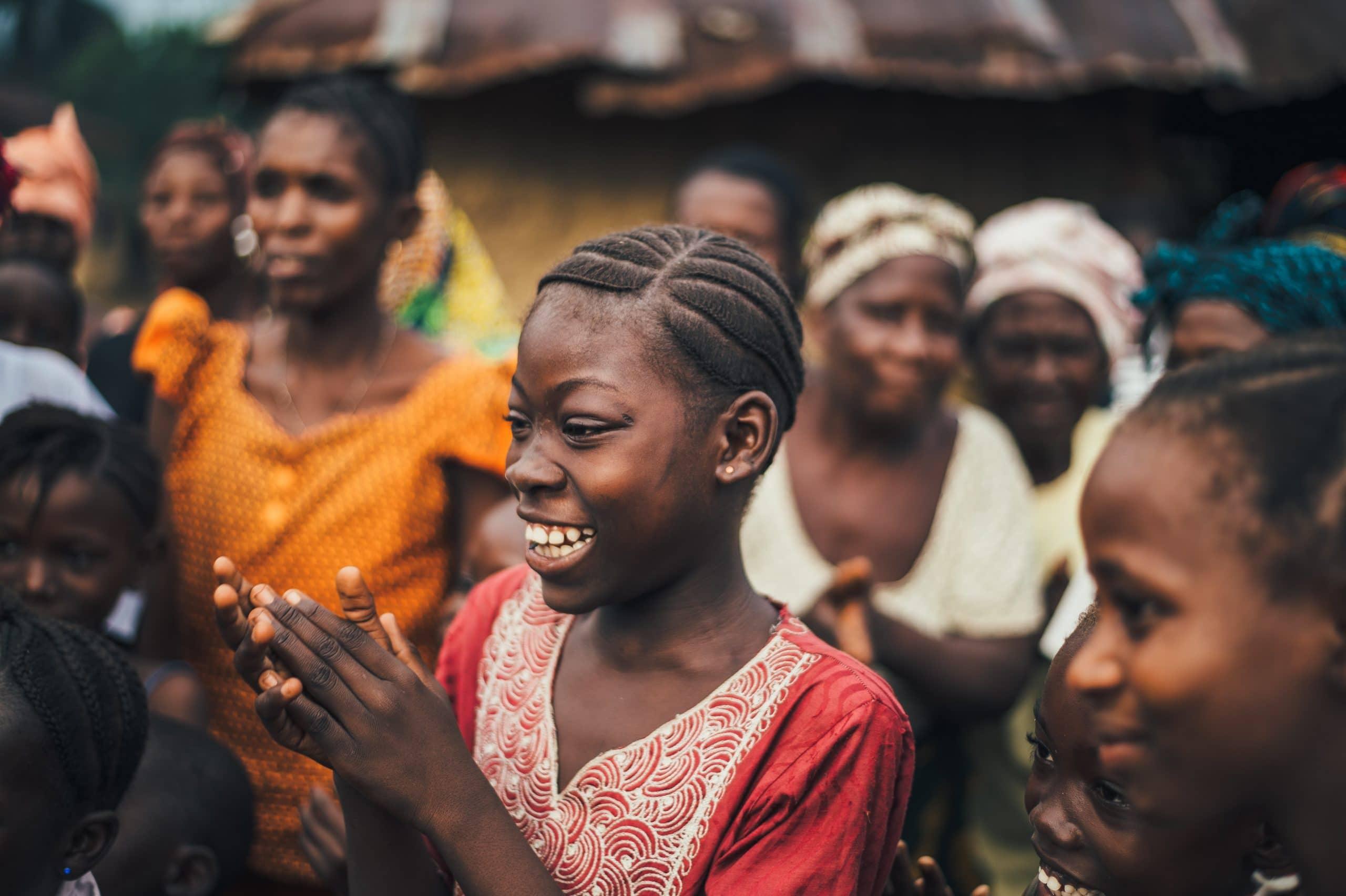 Mulher sorrindo com suas mãos unidas ao redor de outras pessoas