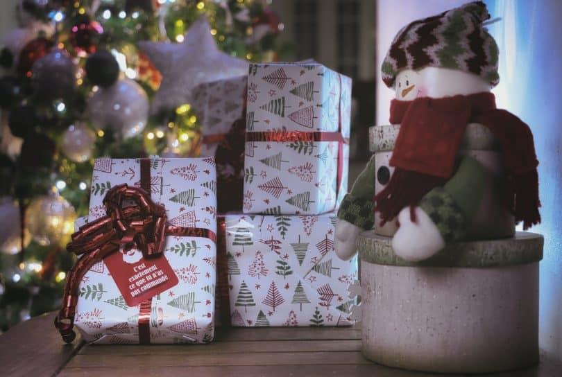 caixas de presentes ao lado de uma árvore de natal