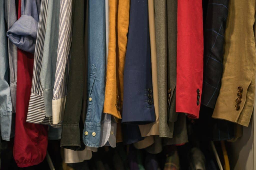 Armário de roupas cheio de camisas e agasalhos pendurados.